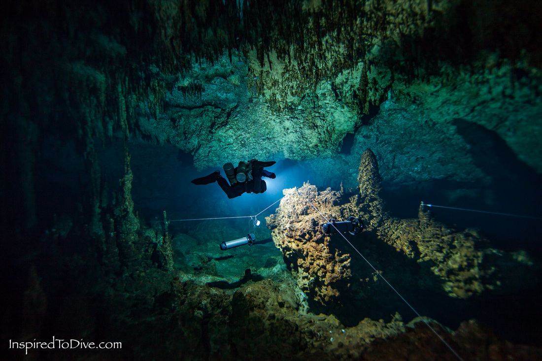 Cave diver with DPVs and reel for mapping caves