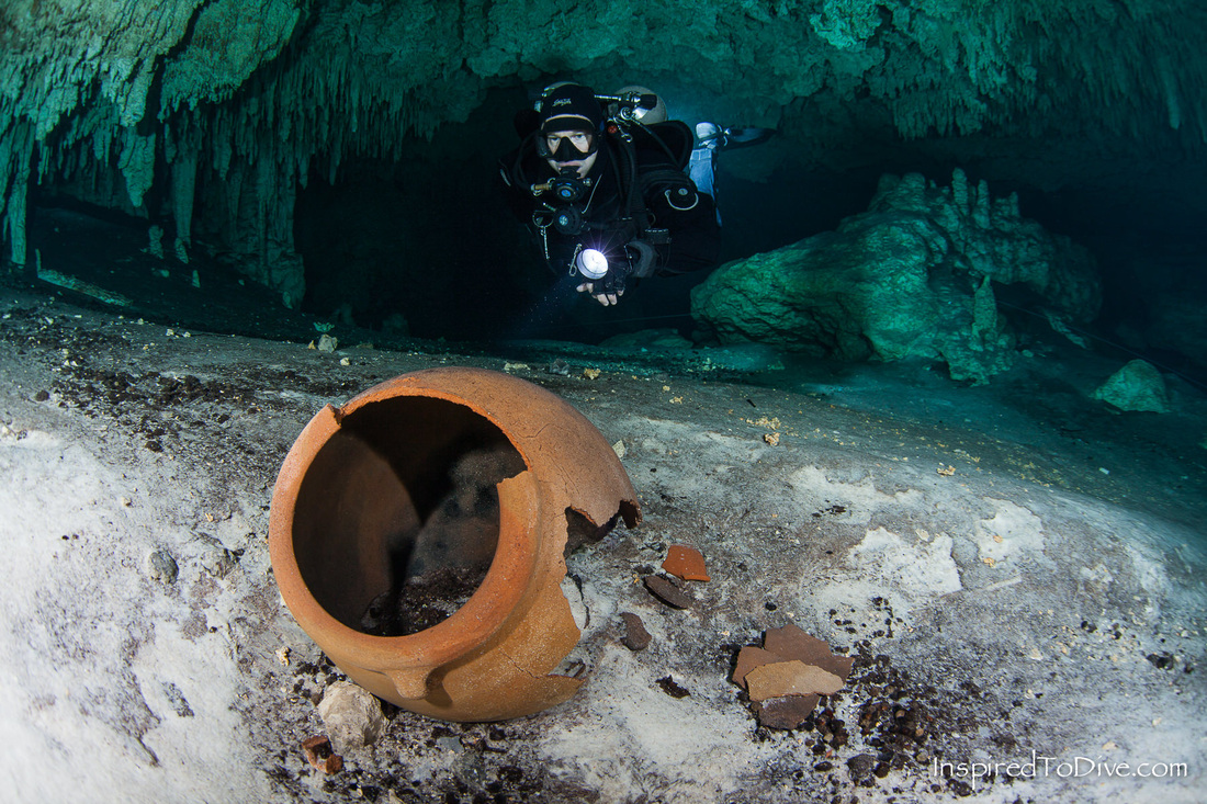 Cave diver with Mayan pot in Sistema Sac Actun in Mexico