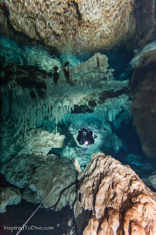 Scuba diver underwater beneath reflective air pocket in a cave in Mexico