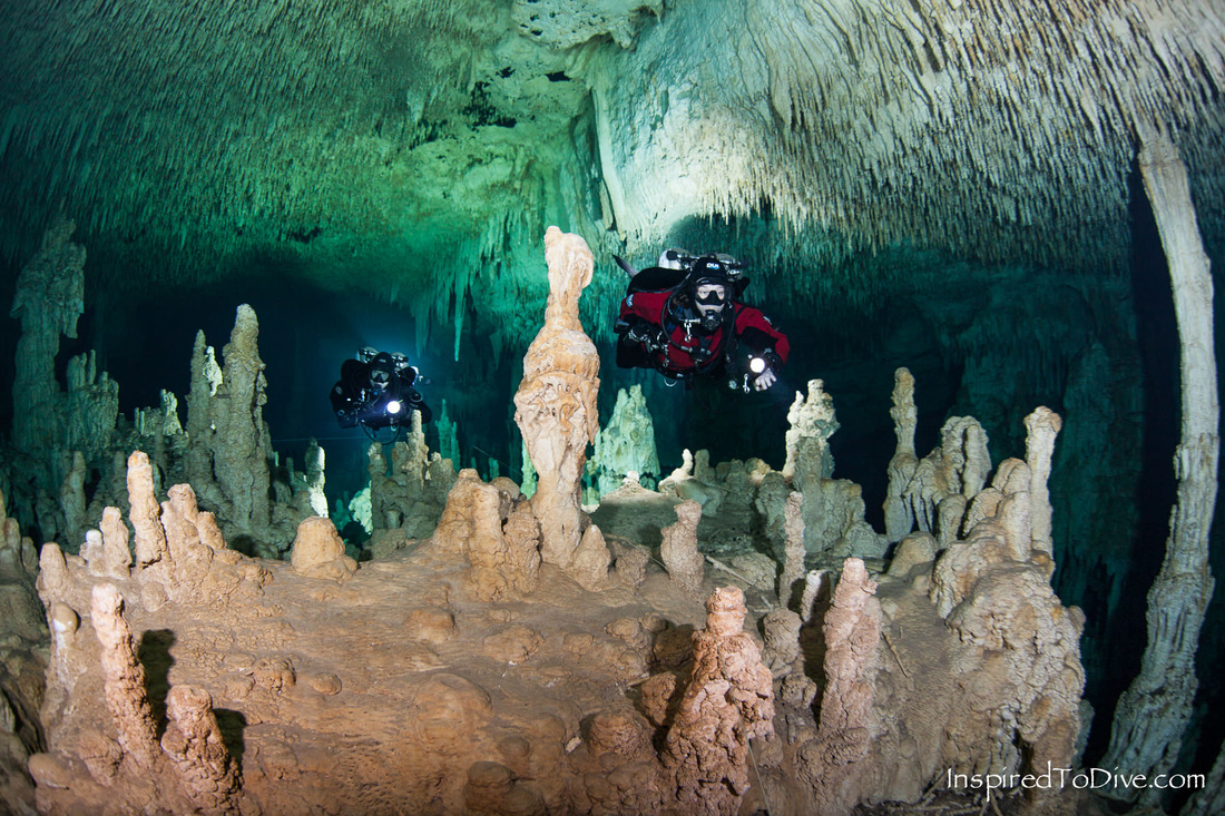 Cave divers underwater in Grand Cenote in Sistema Sac Actun in Mexico